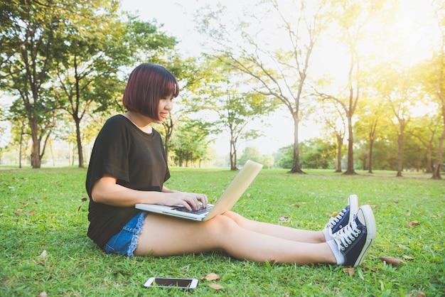 Jovens pernas da mulher asiática na grama verde com laptop aberto Foto Premium