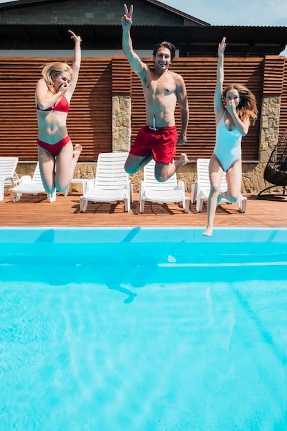 Jovens pulando na piscina Foto gratuita