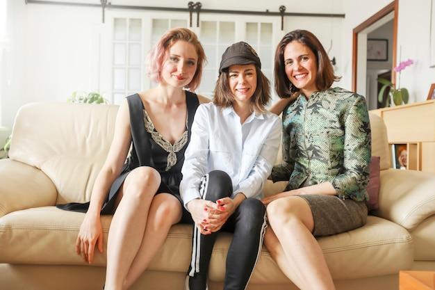 Jovens senhoras bonitas no sofá de couro Foto Premium