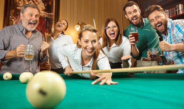 Jovens sorrindo, homens e mulheres jogando bilhar no escritório ou em casa, depois do trabalho. colegas de trabalho envolvidos em atividades recreativas Foto gratuita