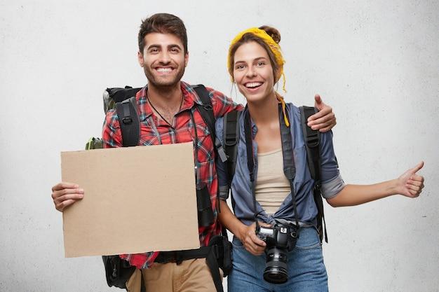 Jovens turistas posando: homem sorridente segurando o cartão em branco e mochila grande, abraçando sua esposa que está segurando a câmera e mochila mostrando sinal okey. turismo, conceito de viagem Foto gratuita