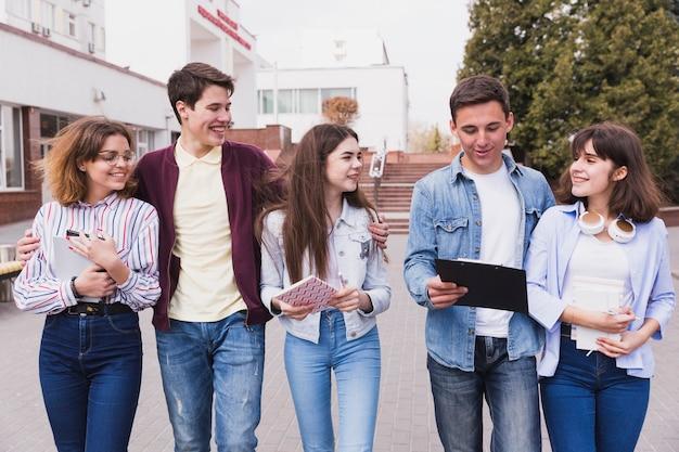 Jovens universitários caminhando juntos Foto gratuita