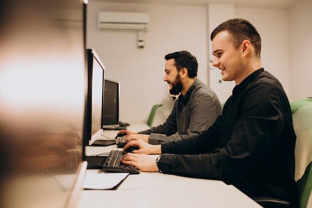 Jovens web designers masculinos trabalhando em um computador Foto gratuita