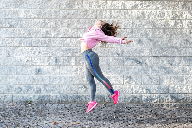 Joyful sporty woman jumping on street Foto gratuita