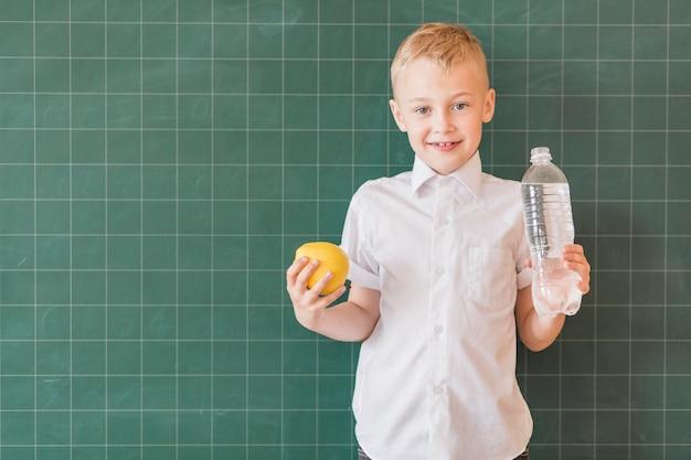 Junior com água e maçã perto de lousa Foto gratuita