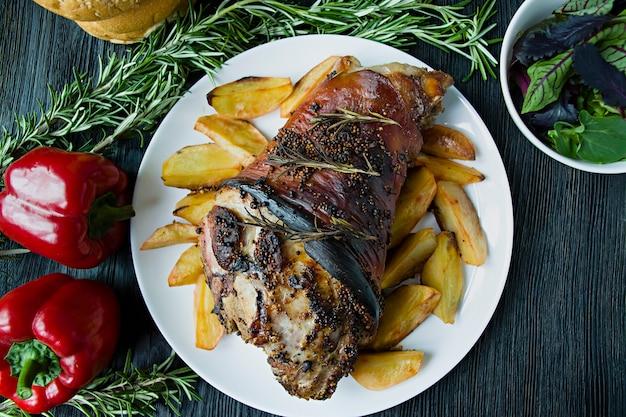 Junta de porco frito com batatas servidas em um prato branco Foto Premium