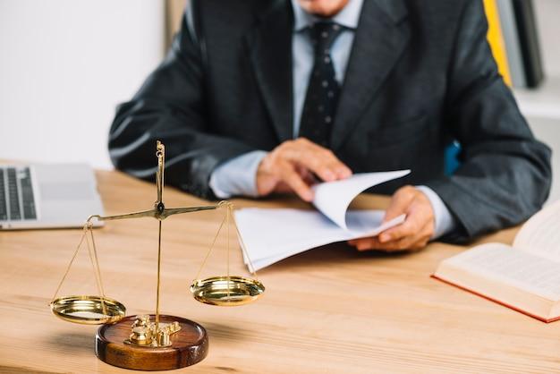 Justiça de escala dourada na frente do advogado virando páginas do documento na sala de tribunal Foto Premium