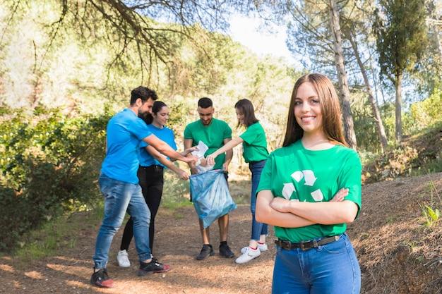 Juventude, dobrando o lixo na floresta Foto gratuita