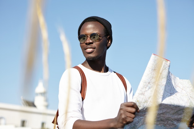 Juventude e férias de verão. mochileiro africano segurando o mapa, examinando novas direções de sua jornada, parecendo alegre, despreocupado e absolutamente feliz, sentindo-se vivo viajando, usando óculos escuros Foto gratuita