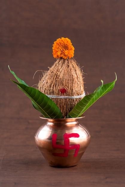Kalash de cobre com coco e manga folha com decoração floral em uma mesa de madeira. essencial no puja hindu. Foto Premium