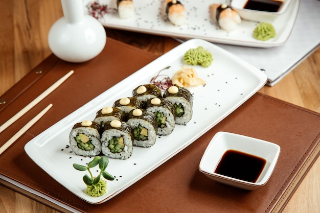 Kappa maki com nori avocafo gengibre wasabi e molho de soja na mesa Foto gratuita