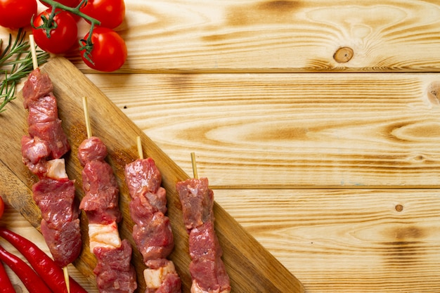 Kebab cru de carne na madeira com legumes. Foto Premium