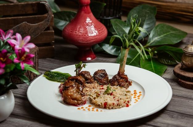 Kebab de carne com guarnição de arroz e sementes de romã Foto gratuita
