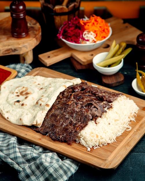 Kebab de carne servido com arroz e pão sírio colocado na tábua de servir de madeira Foto gratuita
