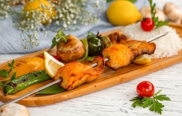 Kebab de esturjão e arroz com legumes fritos Foto gratuita