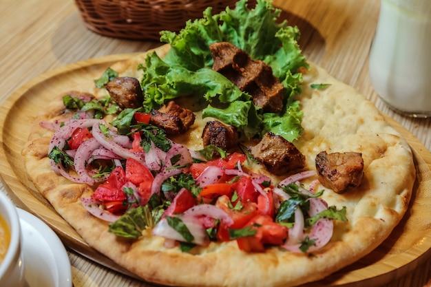 Kebab de frango de vista lateral com cebola tomate e ervas no pão tandoor Foto gratuita