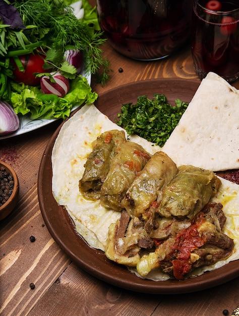 Kelem dolmasi, folhas de couve recheadas com carne e arroz, com ensopado de carne com legumes em lavash. Foto gratuita
