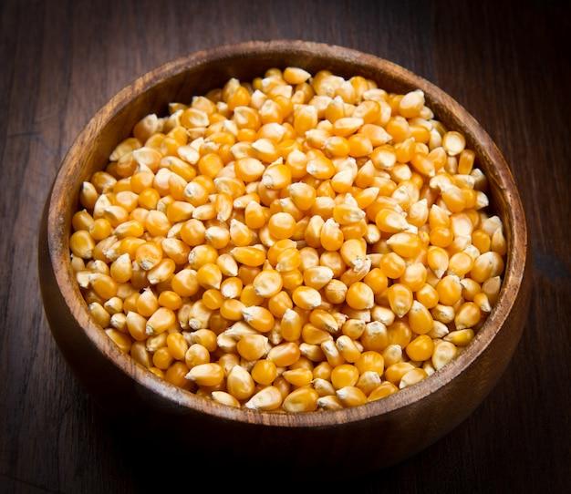 Kernels, sementes de milho na tigela de madeira Foto Premium