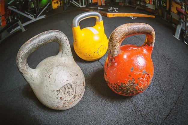 Kettlebell três diferente em um assoalho no centro de esportes da aptidão do gym. Foto Premium