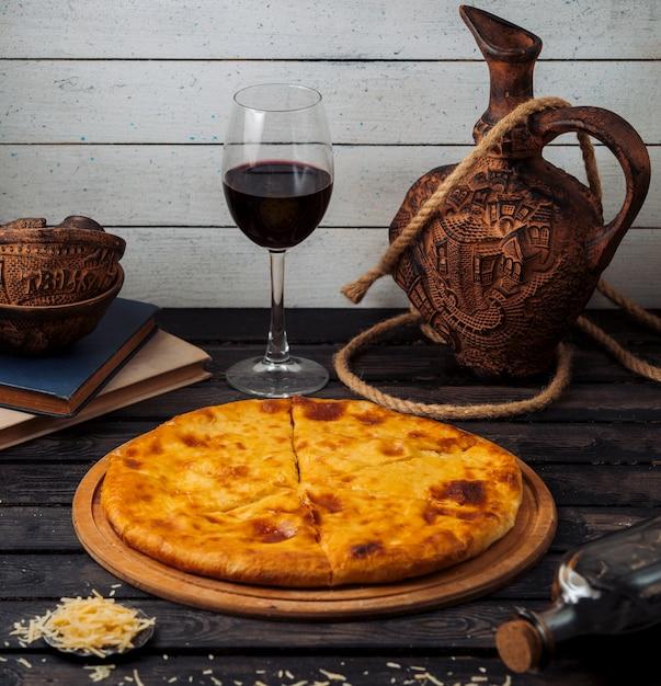 Khachapuri georgiano servido na tábua de pizza de madeira com vinho tinto Foto gratuita