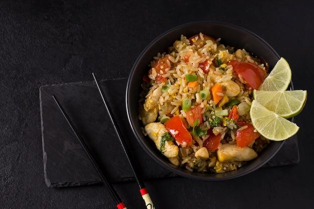 Khao pad, arroz frito com legumes, carne e ovos, com pepinos frescos, tomates, com pauzinhos. Foto Premium