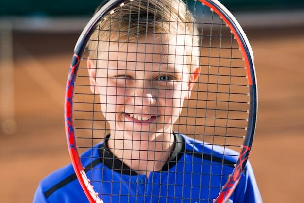 Kid cobrindo o rosto com uma raquete de tênis Foto gratuita