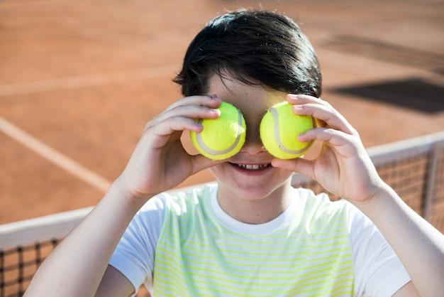 Kid cobrindo os olhos com bolas de tênis Foto gratuita