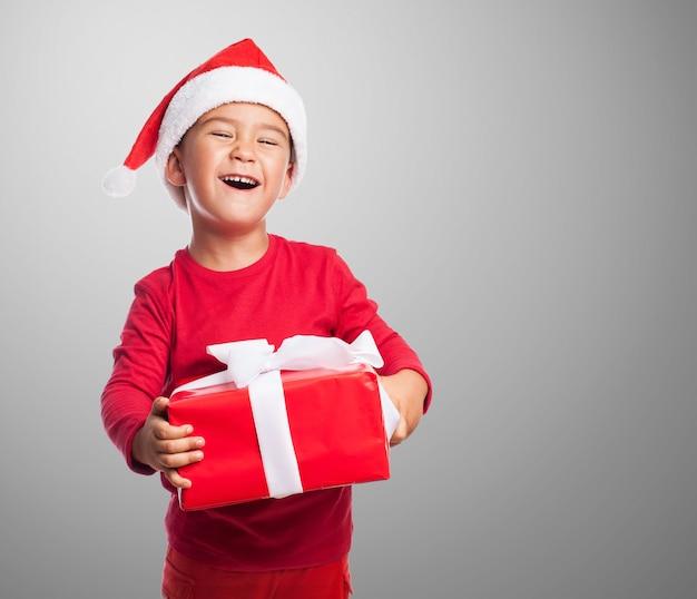 Kid com uma cara engraçada que prende um presente Foto gratuita