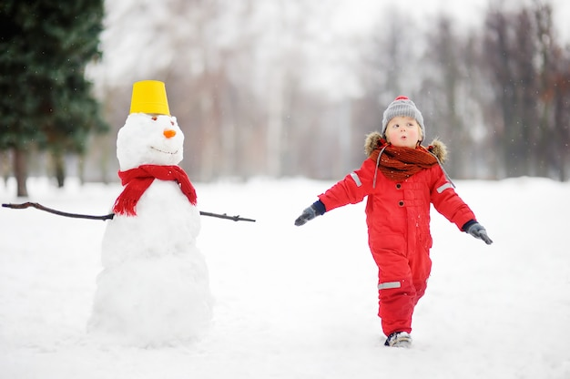 Kid durante passeio em um parque de inverno nevado Foto Premium