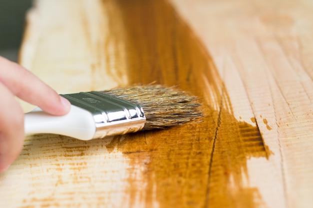 Kid hand varnishing uma prateleira de madeira usando pincel Foto gratuita