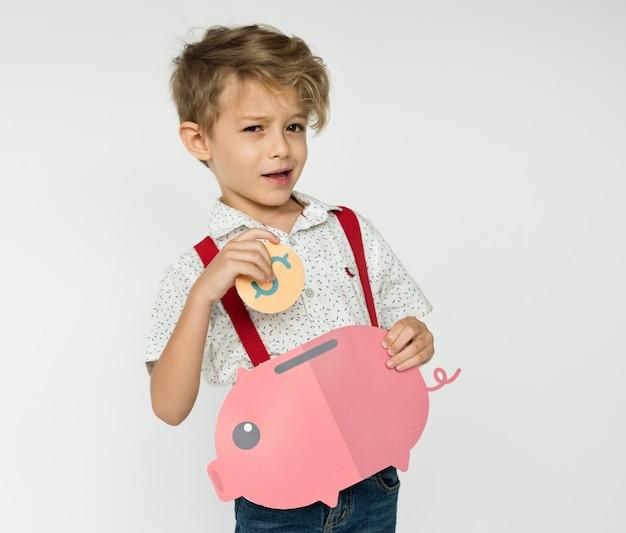 Kid holding piggybank poupar dinheiro Foto Premium