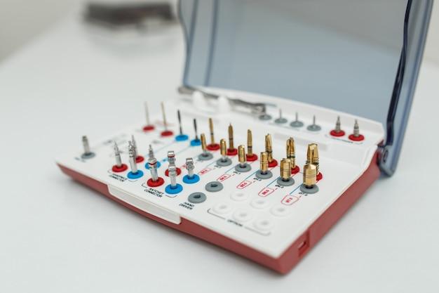 Kit de ferramentas de próteses dentárias em fundo branco Foto Premium
