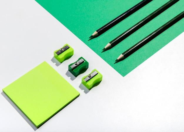 Knolling conceito com notas autoadesivas e acessórios em tons de verde Foto gratuita