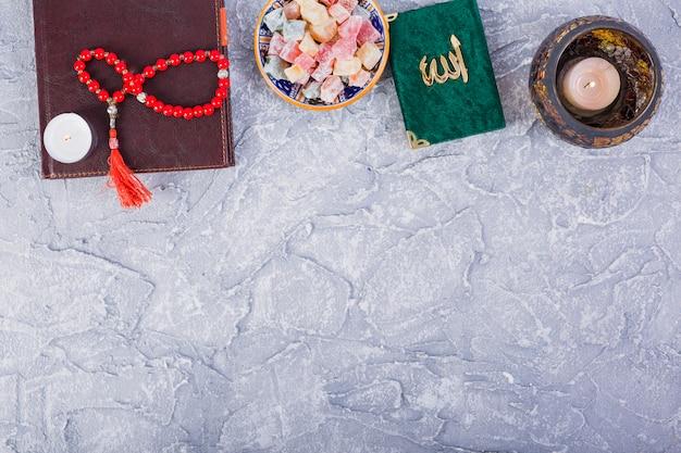 Kuran tradicional; contas de oração; vela acesa com múltiplos rakhat-lukum em pano de fundo concreto Foto gratuita