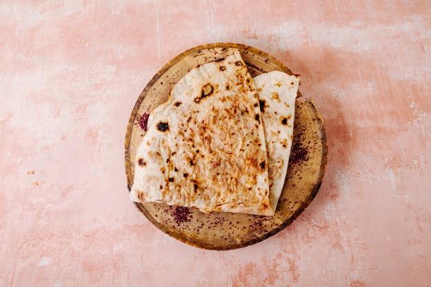 Kutab de lavash caucasiano com tempero sumakh em um pedaço de madeira em um plano de fundo texturizado. Foto gratuita