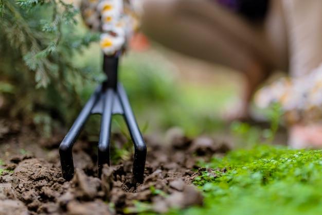La mano de una mujer excava el suelo y la tierra. primer plano, concepto de jardinería, jardinería. vista a nivel del suelo de la mujer que planta las flores en luz del sol. herramientas de jardinería en el jardín. floreria de mujer trabajando en su invernadero. trabajando en el jardín. guantes de trabajo, herramienta de jardín Foto Premium