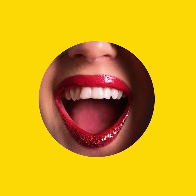 Lábios vermelhos, sorriso brilhante através do buraco no fundo de papel amarelo. compõem o conceito de artista Foto Premium