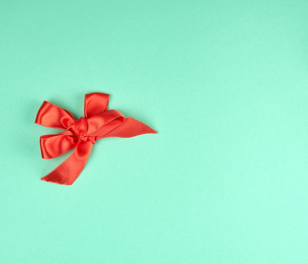 Laço atado de fita de seda vermelha sobre um fundo verde Foto Premium
