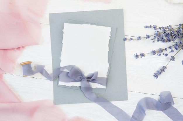 Laço de fita de cartão em branco branco sobre um fundo de tecido rosa e azul com flor de lavanda Foto Premium