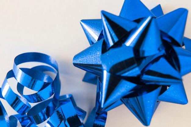 Laço de fita decorativa mancha azul sobre fundo branco Foto gratuita