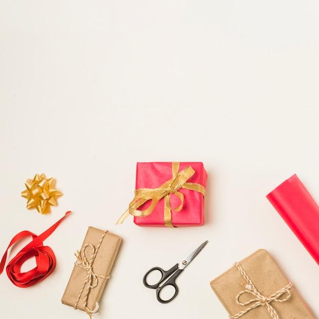 Laço vermelho; arco; tesoura e rolo de papel de embrulho com caixas de presente embrulhado isoladas no fundo branco Foto gratuita