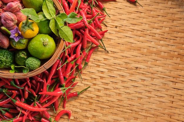 Lado esquerdo da bandeira isolada de ingredientes alimentares tailandeses tradicionais na cesta, pimentões secos, cebola vermelha pequena, limão e vegetais tailandeses, layout deitado no padrão de madeira cremalheira tradicional tailandesa de madeira Foto Premium