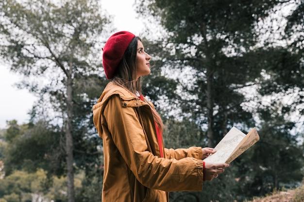 Lado, vista, jovem, mulher, segurando, mapa, mão, ficar, floresta Foto gratuita