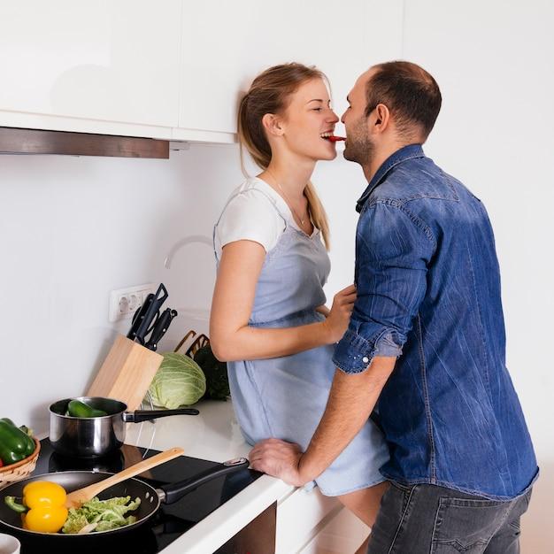 Lado, vista, jovem, par, comer, cenoura, junto, cozinha Foto gratuita