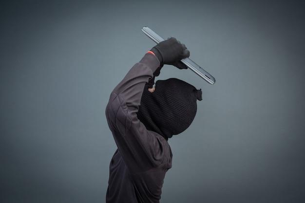 Ladrões masculinos roubam um computador portátil em cinza Foto gratuita