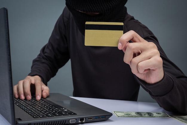 Ladrões seguram cartões de crédito usando um laptop para atividades de hacking de senhas. Foto gratuita