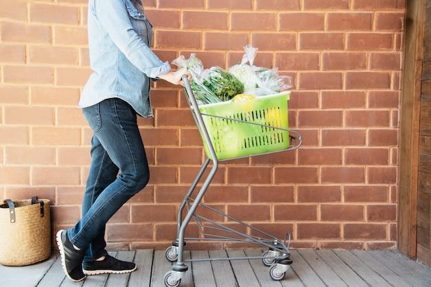 Lady está comprando vegetais frescos na loja de supermercado Foto gratuita