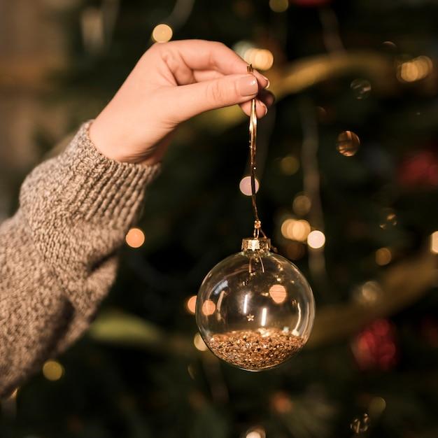 Lady segurando ornamento bola de natal transparente Foto gratuita