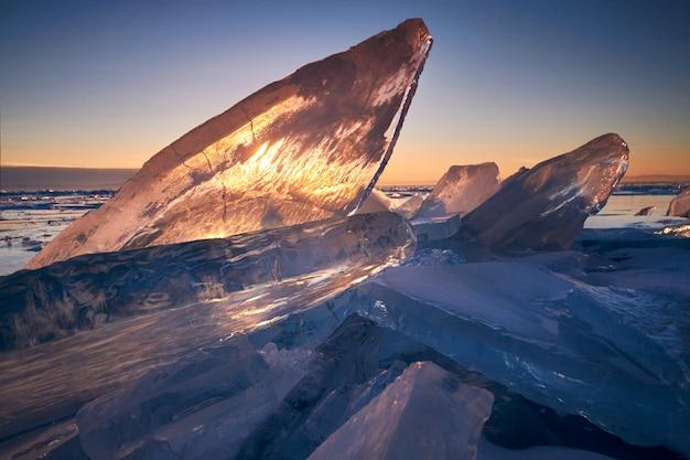 Lago baikal ao pôr do sol, tudo está coberto de gelo e neve, gelo azul claro e espesso Foto Premium