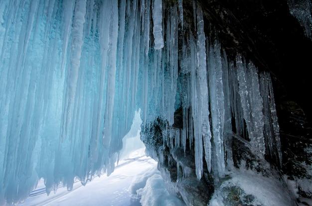 Lago baikal é um dia gelado de inverno. maior lago de água doce. o lago baikal está coberto de gelo e neve, frio e geada fortes, gelo azul claro e espesso. pingentes pendurados nas rochas. lugar incrível herança Foto Premium